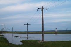 Översvämmat fält och elektriska poler efter storm Royaltyfri Fotografi