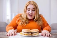 Översvallande fet kvinna som äter småfiskar och smörgåsar arkivfoton