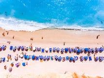 Överträffa ner sikt av en strand med turistsuntbeds och paraplywi arkivfoton