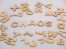 Överträffa ner sikt på träbokstäver med ordkaoset arkivfoto