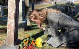 Överväldigad av sorg lady med blommor på graven Arkivfoto