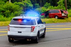 Övervaka blinkande blåa ljus på den skadade bilen för olyckan arkivfoto