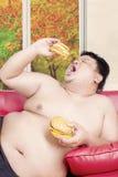 Övervikt med två stora hamburgare Royaltyfria Bilder