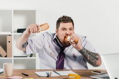 överviktig affärsman som äter hotdogs på arbetsplatsen Arkivfoto