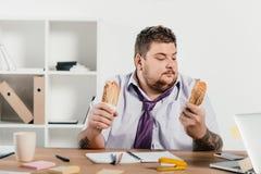 överviktig affärsman som äter hotdogs på arbetsplatsen Royaltyfri Fotografi