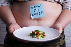 Överviktig fet kvinna med lite delen av mat som frågar hur till arkivfoton