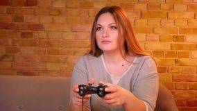 Överviktig hemmafru som spelar videospelet genom att använda styrspaken som den är mycket uppmärksam och hipped i hemtrevligt hem lager videofilmer