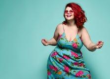 ?verviktig kvinna f?r lycklig plus-format dam i den lyckliga dansen f?r modesolglas?gon som och f?r f?rgrika sundress firar arkivfoton
