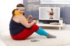 Överviktig kvinna som äter att le för chokladcake arkivfoto