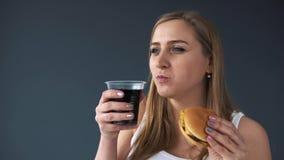 Överviktig kvinna som äter en hamburgare och drinkar en sodavatten på den gråa bakgrunden Kameran flyttar nedåt uppvisning arkivfilmer