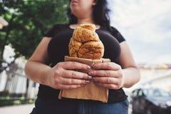 Överviktig kvinna som äter gifflet som utomhus går Royaltyfri Bild