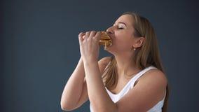 Överviktig kvinna som äter hamburgaren på grå bakgrund Begreppet av skadlig mat, överskottvikt arkivfilmer