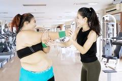 Överviktig kvinna som gör en elasticitet med hennes instruktör Royaltyfria Foton