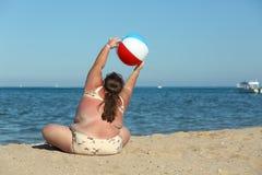 Överviktig kvinna som gör gymnastik på stranden arkivfoton