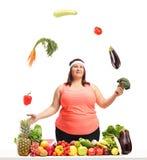 Överviktig kvinna som jonglerar grönsaker bak en tabell med frukt a Royaltyfri Fotografi