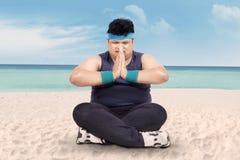 Överviktig man som gör yoga på strand 1 Arkivfoto