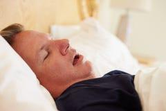 Överviktig man sovande, i att snarka för säng Royaltyfri Fotografi