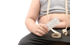 Överviktig pojke med den sjukligt feta buken som tar bantningpreventivpillerar royaltyfria bilder