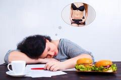 Överviktig sjukligt fet kvinna med skräpmat som sover och drömmer av f arkivfoton