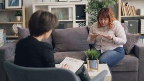 Överviktig ung dam som upp till öppnar den erfarna psykologen under konsultation