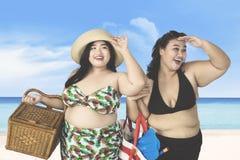 Överviktiga kvinnor som ser något på stranden Royaltyfri Bild
