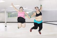 Överviktiga kvinnor som tillsammans hoppar i idrottshall Arkivbilder
