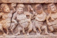 Överviktigt folk för dans på stenlättnad av den 7th århundradetemplet i den Badami staden, Indien Royaltyfri Foto