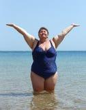 Överviktigt kvinnaanseende i havet på stranden Royaltyfri Foto