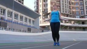 Överviktigt kvinnligt hoppa rep på sportjordning lager videofilmer