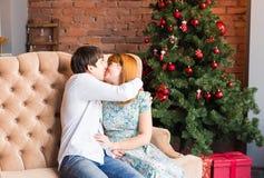 Övervintra, älska, koppla ihop, jul- och folkbegreppet - mannen och kvinnan som kysser över bakgrund för julträd arkivfoto