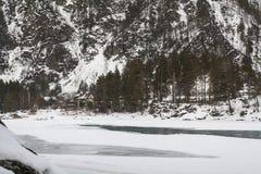 Övervintra bergfloden under is och kust- stenar arkivbilder