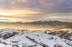 Övervintra bergsikten på gryning, strålarna för sol` s skiner överkanten av mountaen Arkivfoto