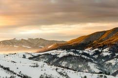 Övervintra bergsikten på gryning, strålarna för sol` s skiner överkanten av mountaen Arkivfoton