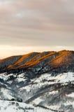 Övervintra bergsikten på gryning, strålarna för sol` s skiner överkanten av mountaen Royaltyfri Bild