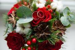 Övervintra bröllopbuketten av röda rosor med vigselringar Arkivfoto