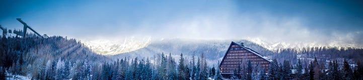 Övervintra den sceniska panoramasikten av berget med ett hotell och skida banhoppningplattformen Arkivfoto