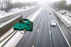 Övervintra den snöig dagsikten av trafikkameran för genomsnittlig hastighet över UK-motorwayen royaltyfria foton