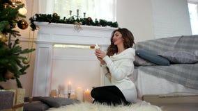 Övervintra flickaljus per stearinljuset, härligt sammanträde för ung kvinna vid spisen nära julgranen, den varma slags tvåsittsso lager videofilmer