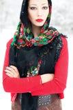 Övervintra flickan i röd kofta med rysssjaletten Arkivfoton