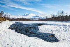 Övervintra floden i norden av Sverige med berg i bakgrund Arkivfoto