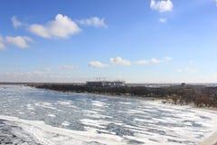 Övervintra floden som täckas med is med blå molnig himmel fotografering för bildbyråer