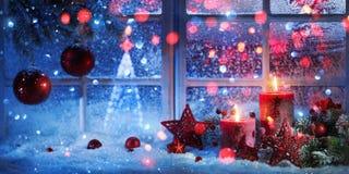 Övervintra garnering med stearinljus nära dettäckte fönstret arkivfoton