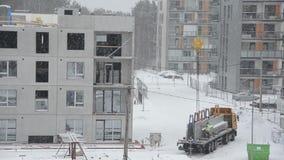 Övervintra häftiga snöstormen och arbetare med delen för huset för kranelevatorkvarteret stock video