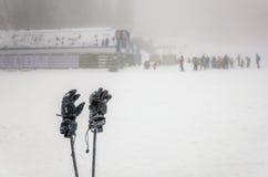 Övervintra handskar och skiipoler med folk som skidar på extrem weath Arkivfoton