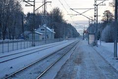 Övervintra järnvägsstationen i en liten by av Lettland Royaltyfri Foto