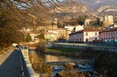Övervintra landskapet av den Adige floden i den Rovereto staden med den medeltida slotten och hus Arkivbild