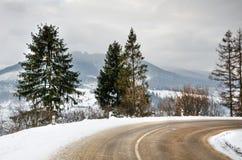 Övervintra landskapet, den snö täckte vägen i bergen med träd Arkivfoton