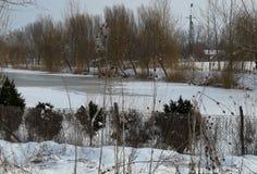 Övervintra landskapet med den djupfrysta kanalen och snöa lite varstans Arkivfoto