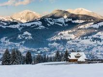 Övervintra landskapet med en ensam stuga på en bakgrund av berg Fotografering för Bildbyråer