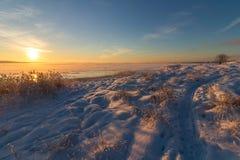 Övervintra landskapet med snö, havet, havet, blå himmel, vägen, solsken, is Fotografering för Bildbyråer